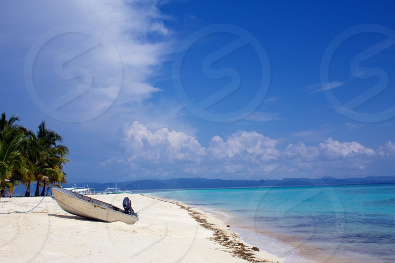 Deserted white sand beach in the Philippines.  Bright blue sky with white clouds. photo