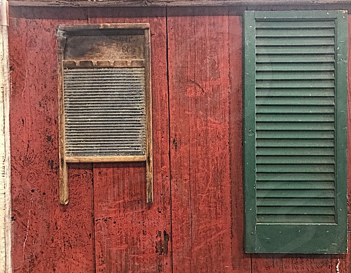 Vintage metal washboard hangs on a red wooden wall near a green shutter. photo