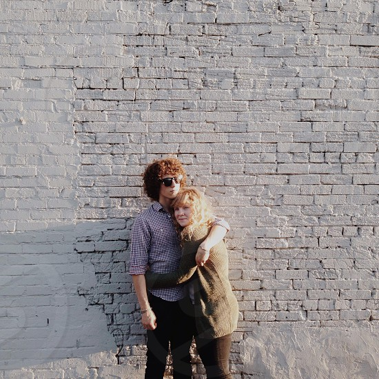 man in grey and white gingham collared button up long sleeve shirt standing by a grey bricked wall hugging a woman photo