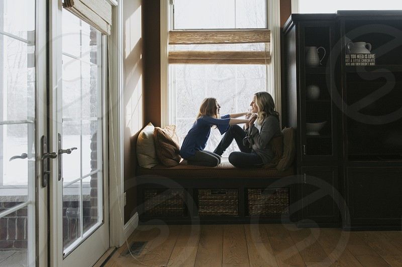 Mother and daughter holding hands and talking in family room in home photo