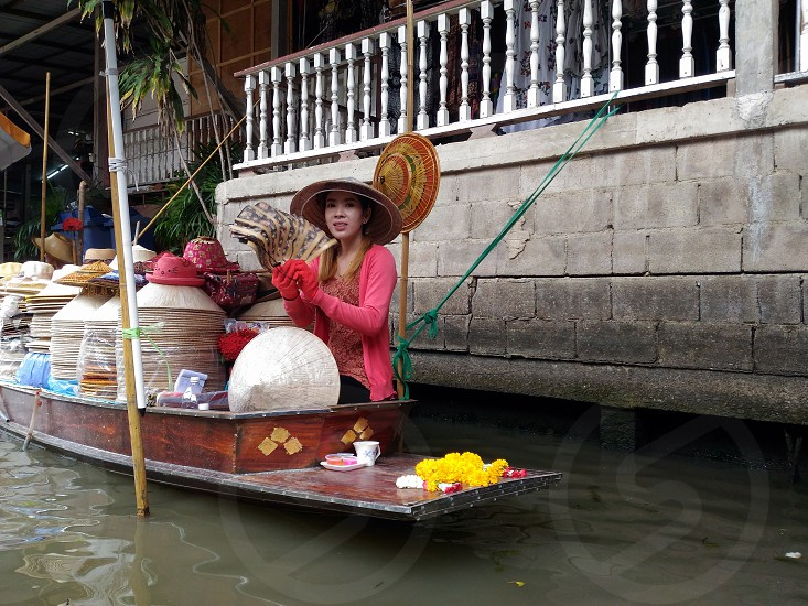 woman selling baskets on brown wooden boat during daytime photo