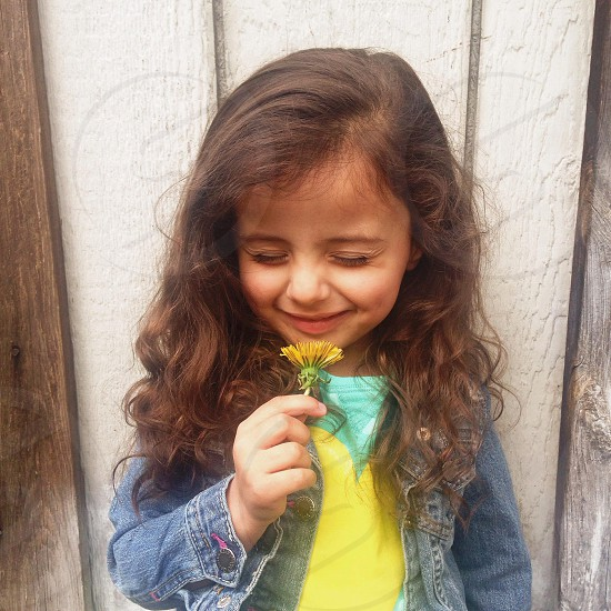 girl holding a yellow flower smiling photo
