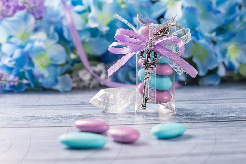 Wedding favors. Boxes with purple and white ribbon containing violet and blue confetti and key gift. photo