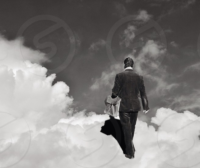 man walking on clouds photo in black and white photo
