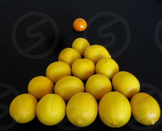 A healthy game of pool or billiards played with a tangerine cue ball and a triangle of meyer lemon balls for a colorful and fun concept for health against a black background copy space. photo