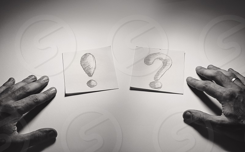 Exclamation and question signs drawn on paper male hands in front.  photo