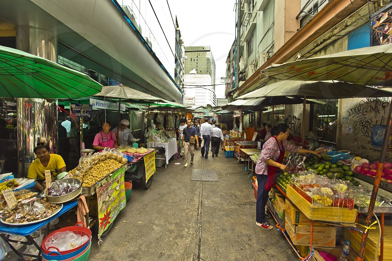 Street market are everywhere in Thailand this one is located on one of the soi of Silom. Sellersvendorstouristbuyersfreshfruitsproducts photo