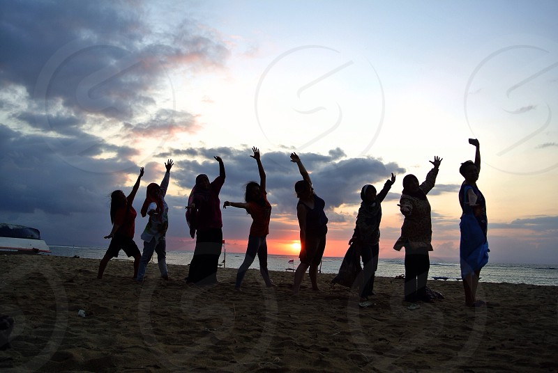 silhouette of 8 women standing near seashore raising their hands while behind their body to right photo