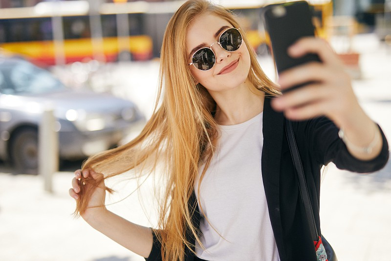 Pretty blonde girl taking selfie on the street photo