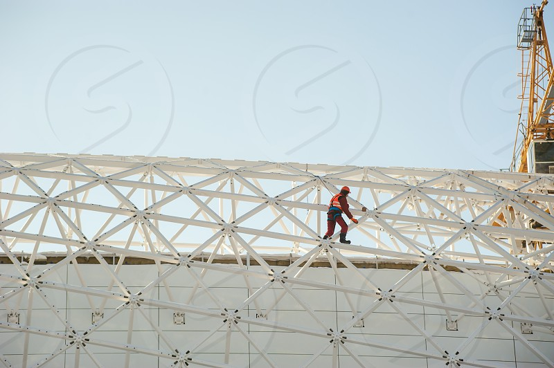 man in overalls  builder fixes on the height. Assembling refurbishment works at altitude with metal structure outdoors against the sky photo
