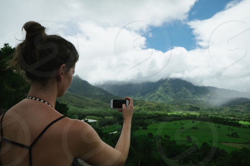 lady taking photo of grassy meadow and mountain photo