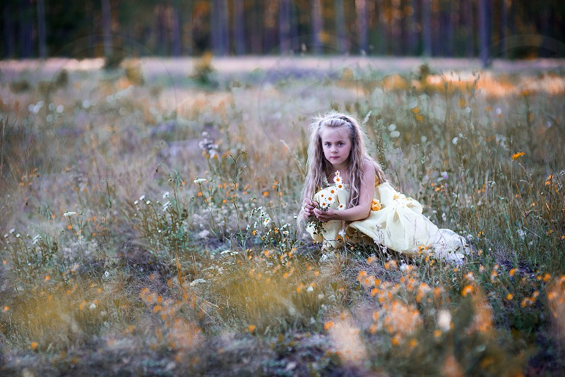 Little girl walking in the forest meadow photo
