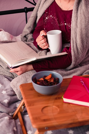 Woman enjoying the reading a book and drinking coffee at home. Young woman sitting in bed wrapped in blanket holding book relaxing at home. Candid people real moments authentic situations photo