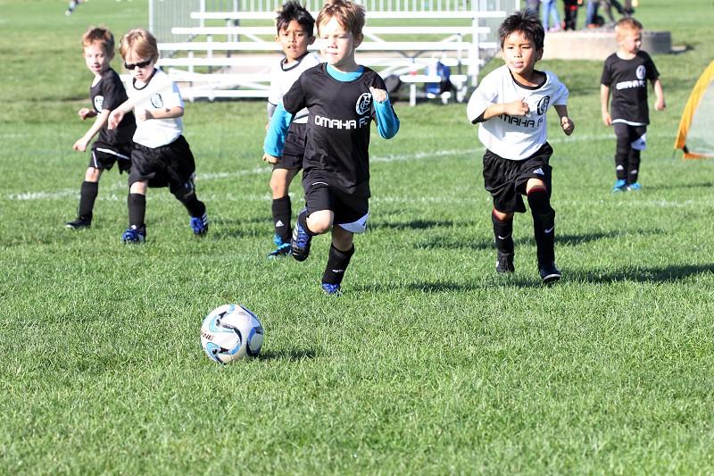 Kids boy son soccer game ball sport kick child children play playing run running grass outdoors outside daytime youth team photo