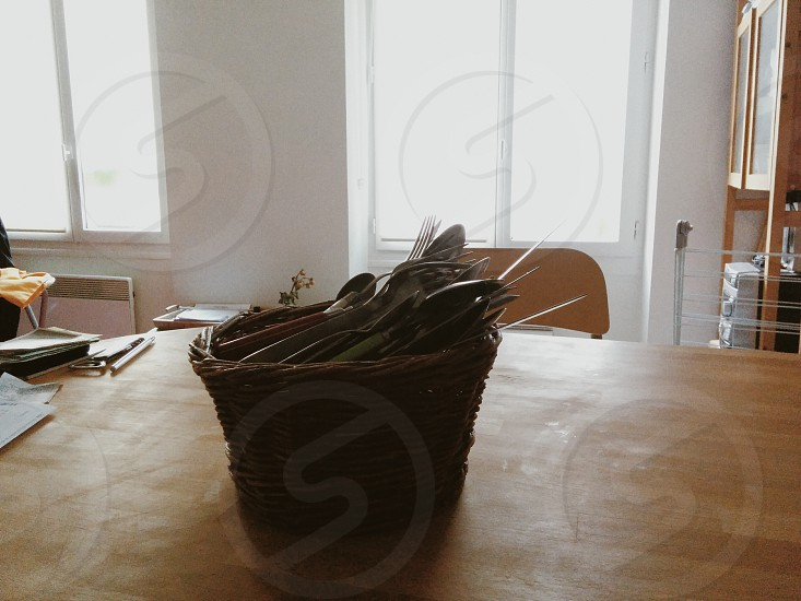 silver spoon and fork in brown wicker basket photo