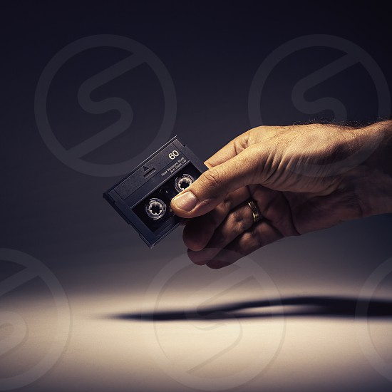 Conceptual composition retro digital technologies digital audio tape in a male hand. photo