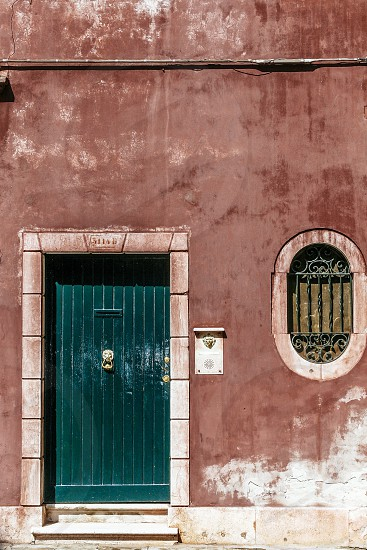 venice building facade door window decaying aged red green patina deteriorating italy house wall photo