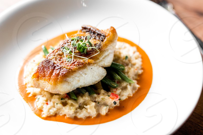 Snapper fish over gold pirloo and haricot verts. Vibrant and bright. photo