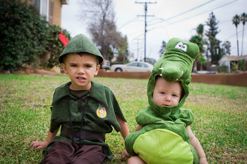 child in peter pan costume sitting beside baby in dinosaur costume photo