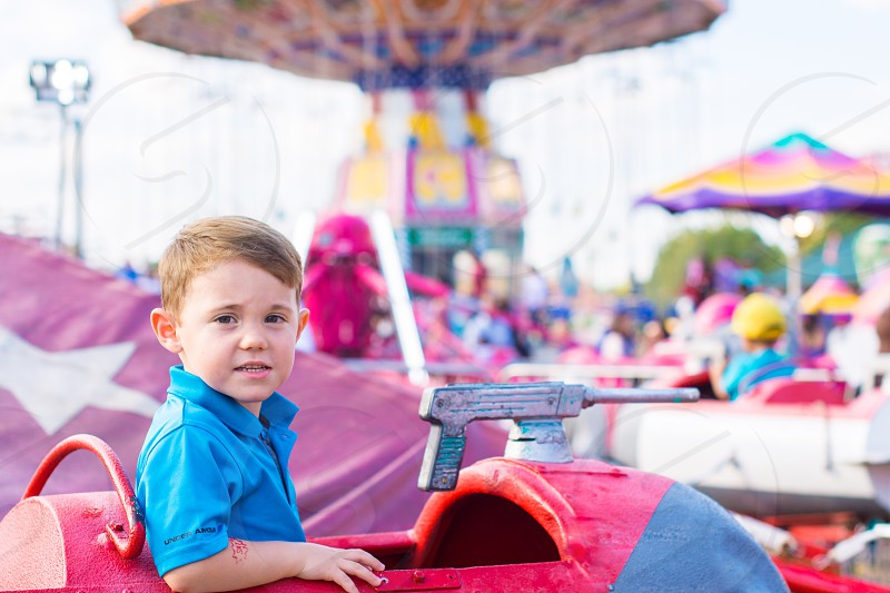 Little boy on a ride at an Amusement park in the summer photo