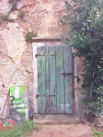 green door on grey stone building photo