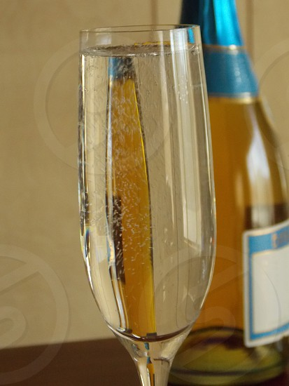 clear liquid in flute glass on brown wooden table photo