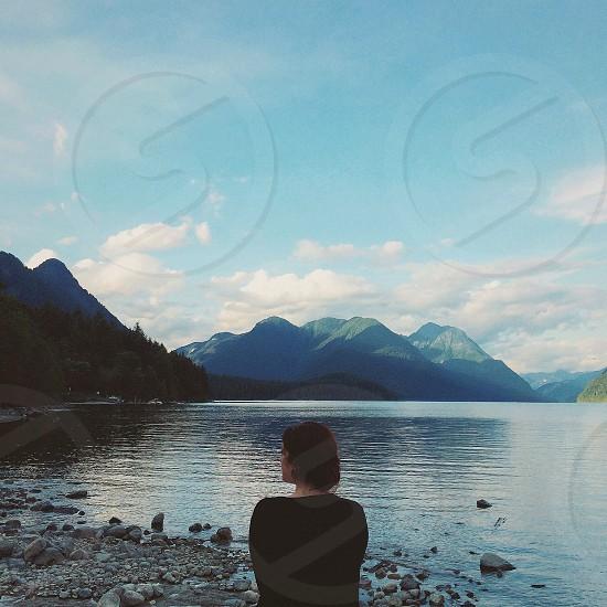 woman sitting facing the sea water photo