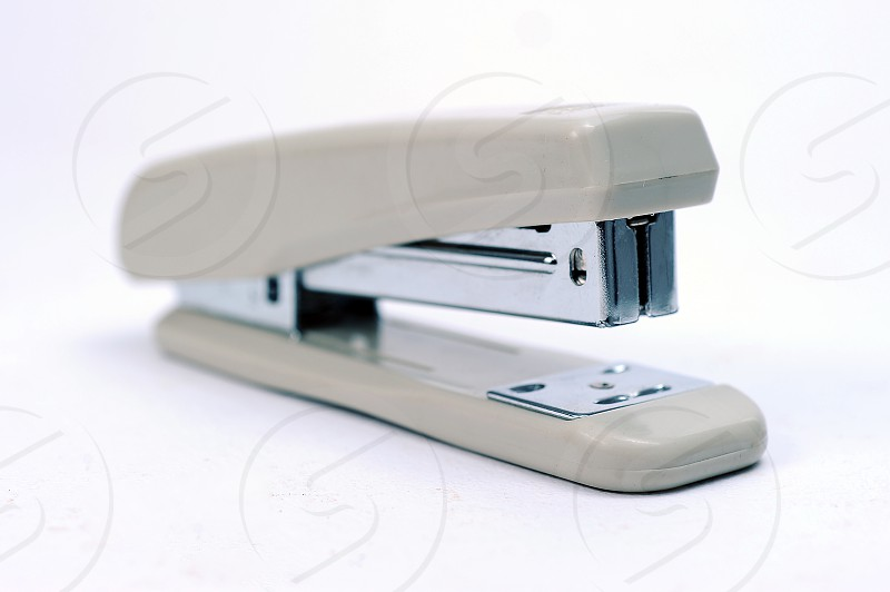 Office stationary Gray stapler with pile of staples isolated on white background with clipping path photo