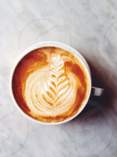 white ceramic mug with leaf print surface photo