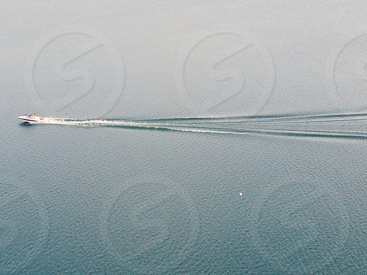 white speed boat with wakes following in water photo