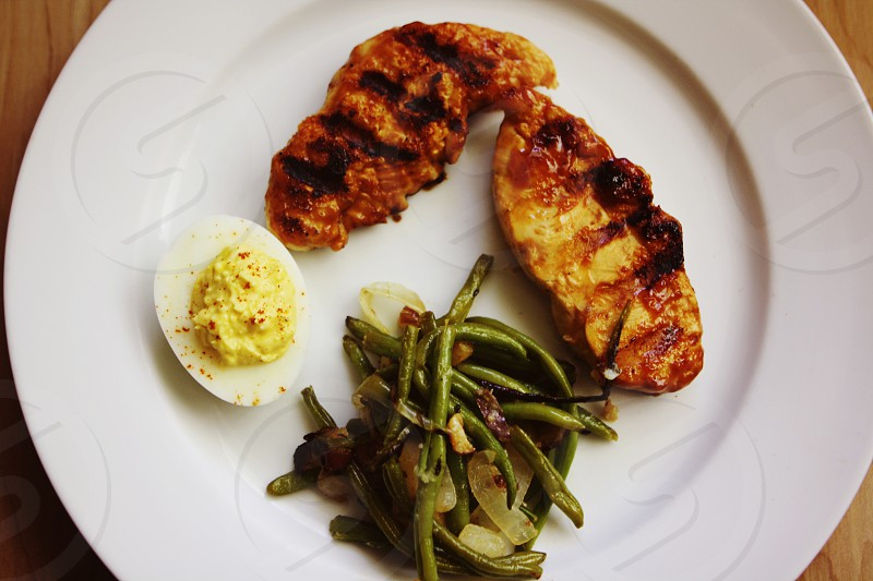 Yummy grilled chicken tenders and sautéed green beans and onions and a deviled egg on the side for flavor photo