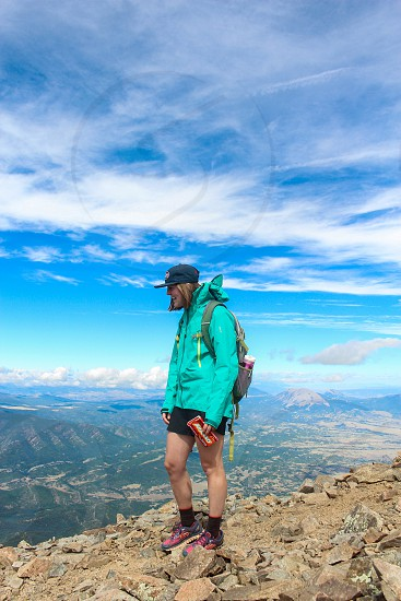 woman in teal jacket standing on top of brown rocky mountain during daytime photo