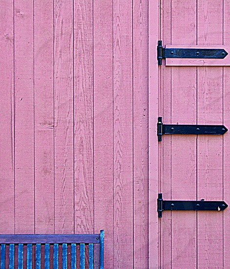 Top edge of a blue bench is seen against a pink wooden shed door with black hinges photo