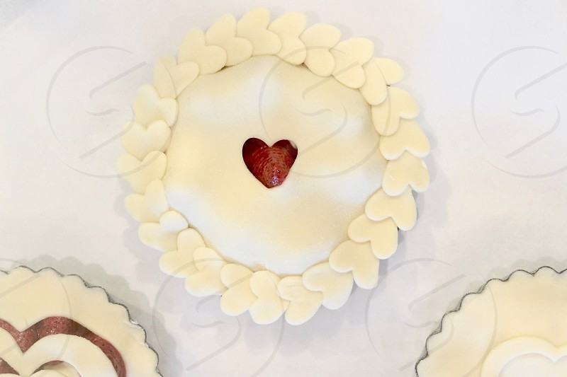 white heart shape icing trim with red hart in the middle pie photo