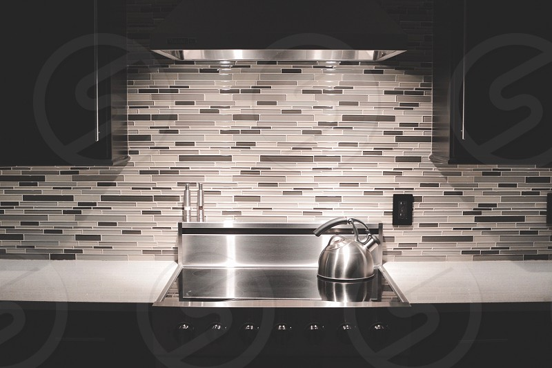 low light photography of a stainless steel teapot on a stainless steel induction range oven near a brown grey and white brick wall photo