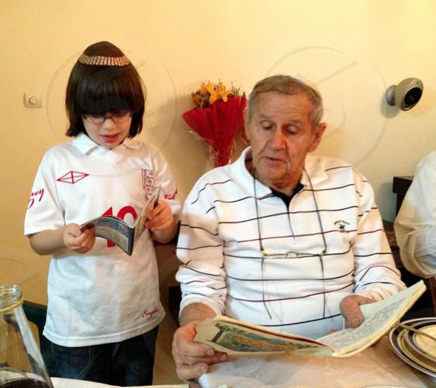 boy standing beside an old man photo