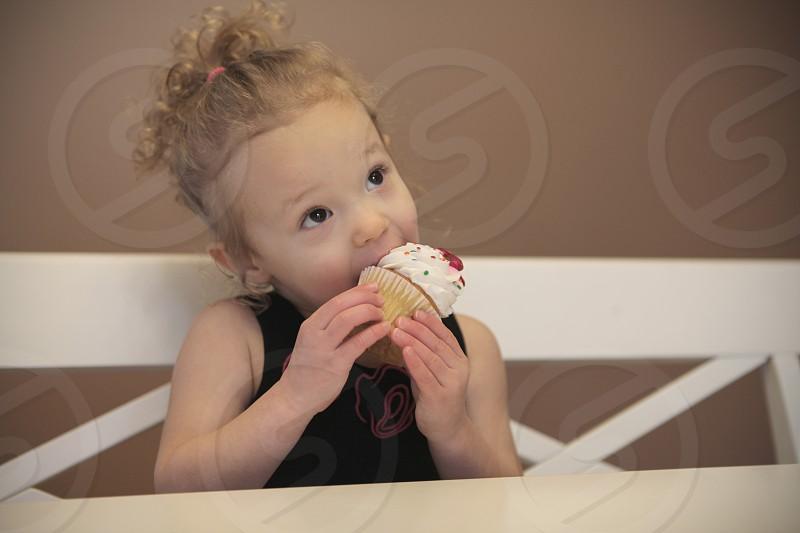 girl in black tank top eating muffin cake photo