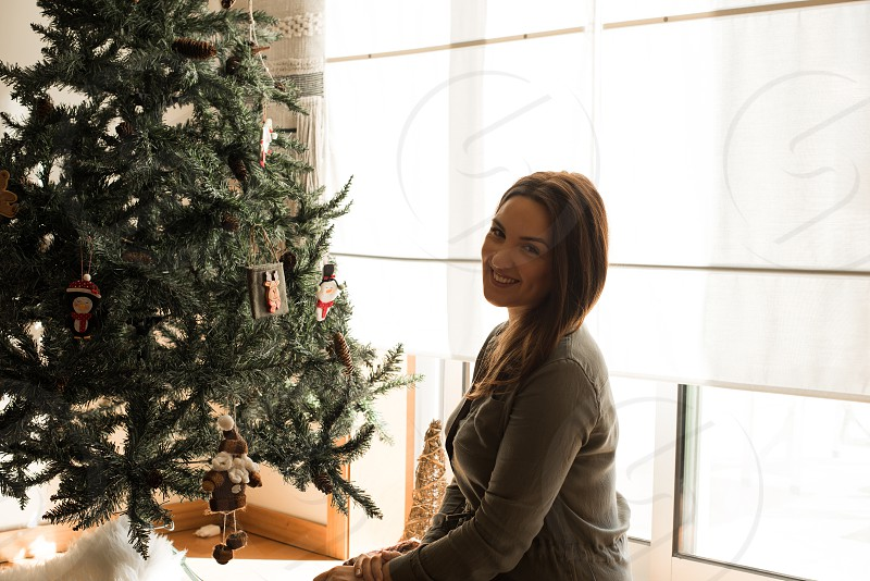 Woman decorating Christmas tree at home photo