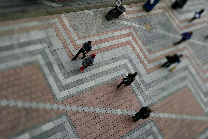 Selective focus from above sidewalks geometric grid people walking blurred ariel drone view photo