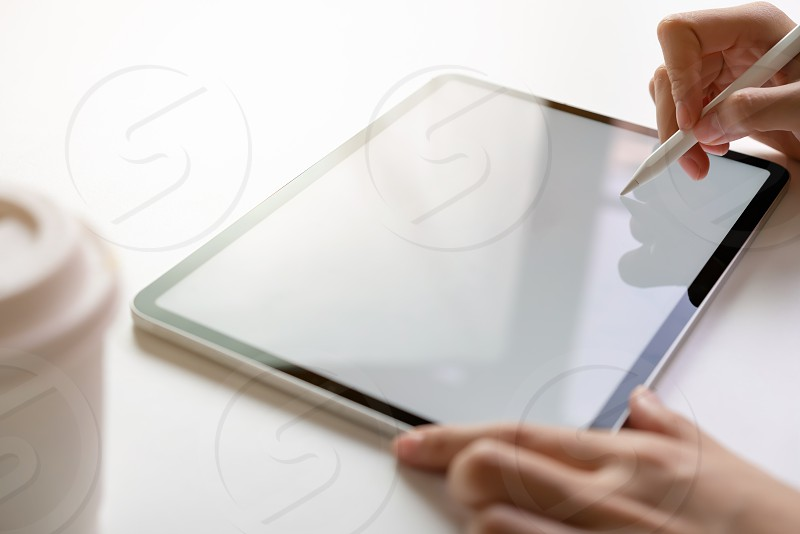 Women hand are using the tablet on the desk. Take your screen to put on advertising. photo