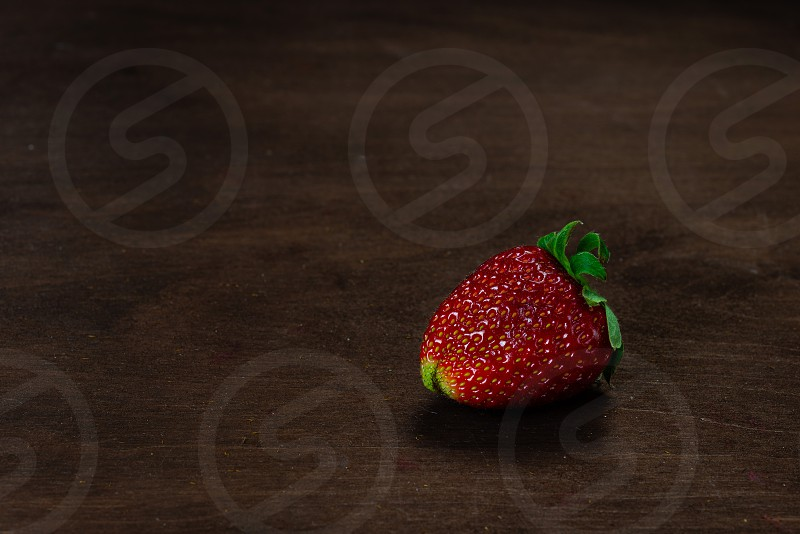 Strawberry on a dark wood background. Creative pattern concept. - Image photo