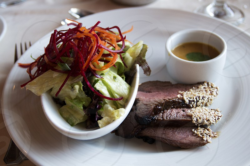 Sliced steak and salad with dressing on white plate photo