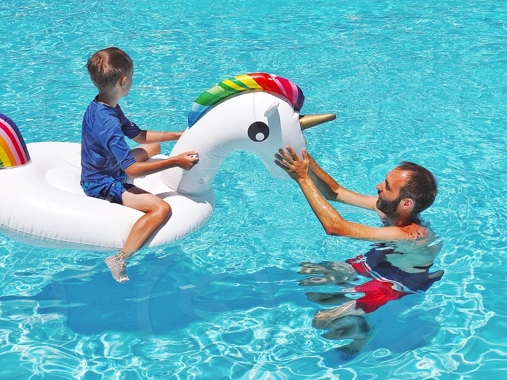 Fatherhood father and son water aqua swimming unicorn pool pool time swimming pool summer summertime summer holidays family fun leisure activity family life lifestyle relax relaxing playing games boy parent parents parents child children hot blue photo