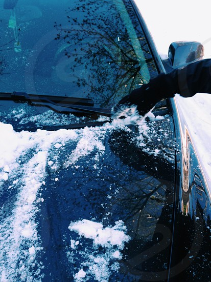 Brushing snow off car windshield during a Winter storm. photo
