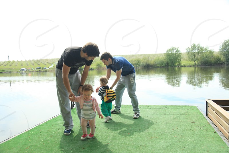 two man holding toddlers on green artificial grass on lake during day time photo