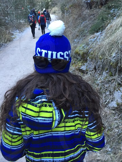 person with black long hair wearing blue and white beanie hat wearing black sunglasses on back of head photo