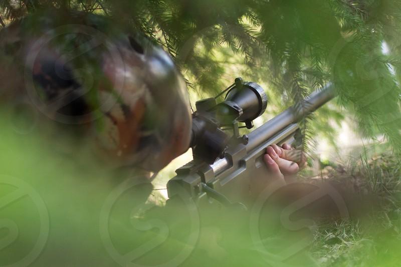 Airsoft sniper taking aim. photo