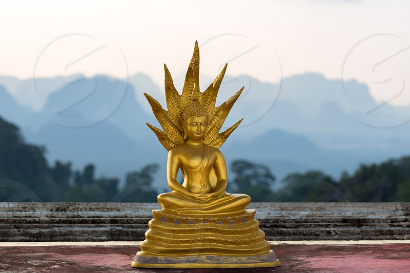 Golden small statue of Buddha in the Wat Tham Suea Tiger cave temple on the background of the silhouettes of the mountains in Thailand photo