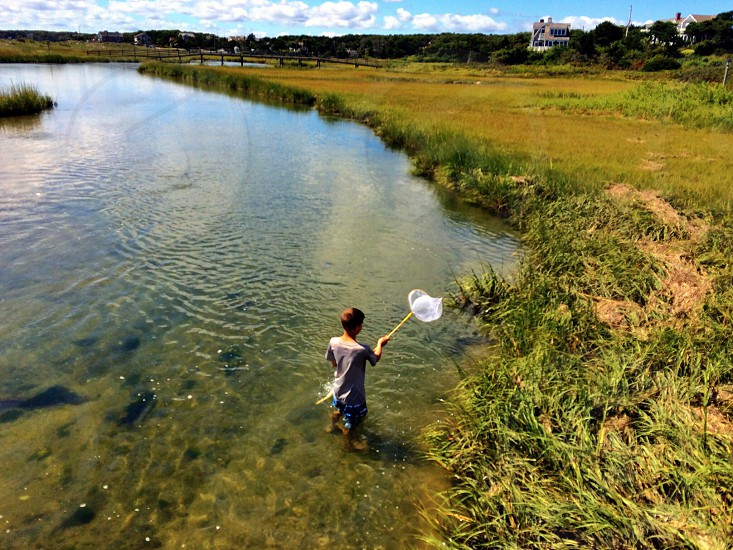 man with white net in grassy area in clear water photo