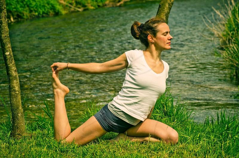 woman doing yoga in grass near water photo